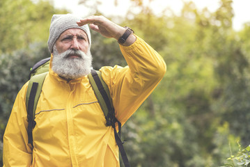 Thoughtful senior male traveler looking at natural scene