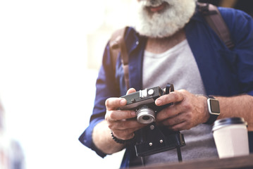 Happy senior male traveler looking at self-made photographs