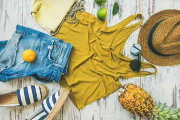 Wall Mural - Colorful summer fashion outfit flat-lay. Denim shorts, straw sun hat, yellow top, espadrillas, leather bag, sunglasses, pineapple, limes and lemon over pastel parquet background, top view