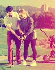 Male golfer explains to the woman  how to play