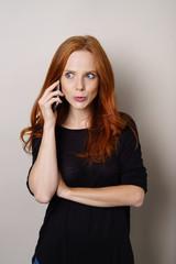 frau telefoniert mit ihrem mobiltelefon und schaut erstaunt zur seite