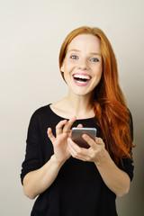 lachende frau hält ihr mobiltelefon in der hand