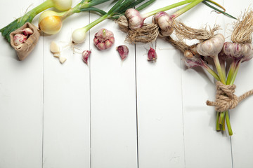 Fresh garlic and onions on a white wooden table.