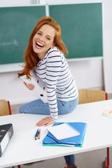 glückliche studentin sitzt in der uni auf dem tisch