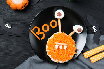 Funny toast with carrots in a shape of monster, sandwich for kids Halloween idea, top view on wooden background