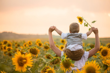 Mother with baby son in sunflower field