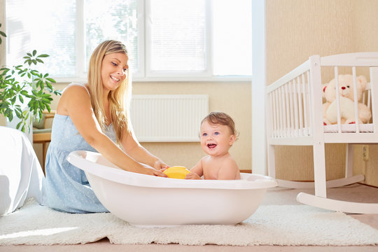 The mother bathes the baby in the bathroom in the room.