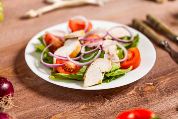 Fresh salad with chicken, tomato and greens on wooden background top view. Healthy food.
