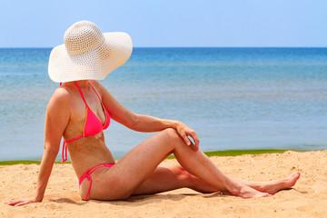 Woman in big straw sunhat sunbathing on a sandy beach. Summer holidays concept