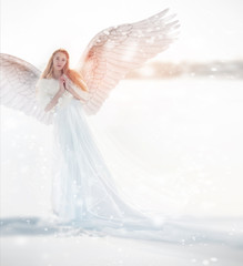 Woman angel with wings in the winter. Snow angel standing in the snow, the Keeper of winter, a fabulous image