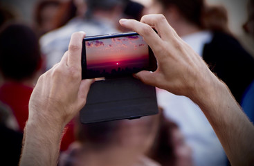 Man´s hands taking photo of the beautiful sunset with a smartphone