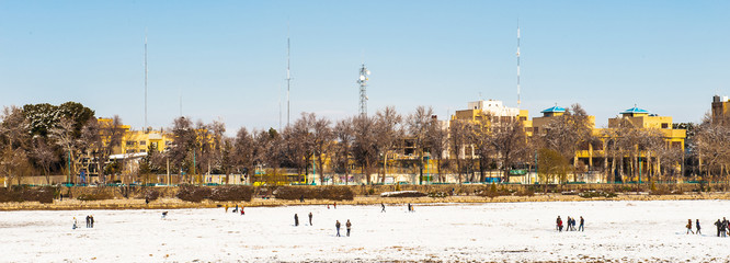 People walking oer the snow near the 33 pol Allah Verdi Khan bridge in Isfahan, Iran