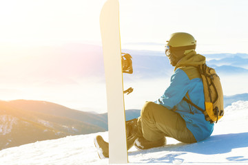 Male snowboarder sitting at the very top of a mountain and taking a look at landscape