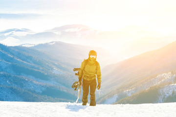 Young snowboarder climbing up the mountain with his board in hand