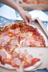 Hand taking ham and cheese pizza slice from box