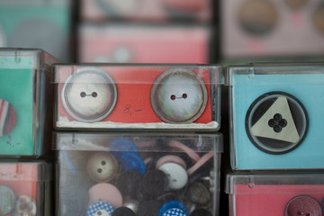 close up of buttons in container. round, plastic, haberdashery, fashion.