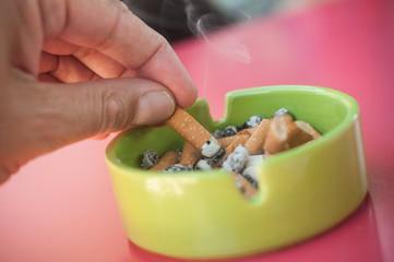 main entrain d'éteindre une cigarette dans un cendrier