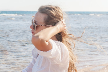 A young woman in sunglasses holds a hand to her hair fluttering