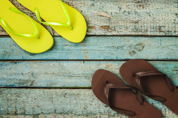 Several pairs of multi-colored rubber flip-flops exhibited in a row on a blue wooden background