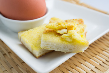 square egg bread in white square plate on bamboo mat background