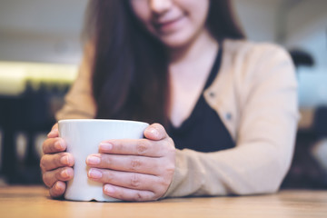 Closeup image of a woman holding a white cup of coffee with two hands in modern cafe