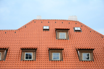 Red ceramic Shingles Roof with attic Windows and Rain Gutter. New house with mansard and skylights windows.
