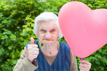 Elderly lady holding a heart shaped balloon