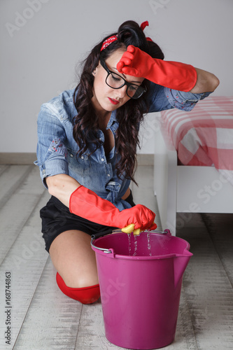 bella ragazza lava i pavimenti a mano\