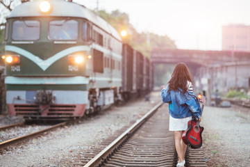 Beautiful girl with guitar walking on railway tracks at railway station