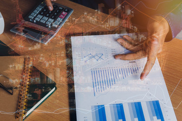 Double exposure of financial and offshore oil and gas platform background concept.  Hand business man work to calculate of finances or banking and accounting on modern rustic wooden office desk.