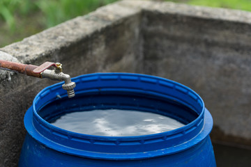 Blue plastic water barrel with rainwater standing near concrete wall