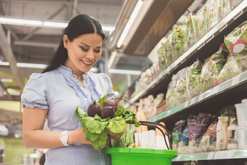 Beaming asian buyer keeping vegetables in hand