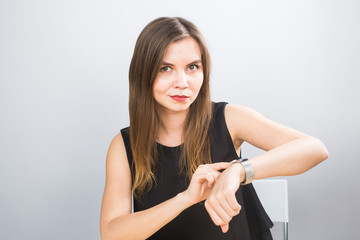 Time is over. Attractive brunette woman pointing to her hand reminding about time