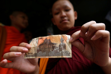 A Buddhist monk holds a riel banknote with the image of Buddha at a store in Phnom Penh