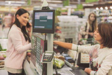 Customer locating near cash desk in supermarket
