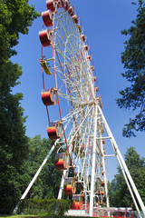 Ferris wheel against a blue sky and green trees in a summer sunny day.