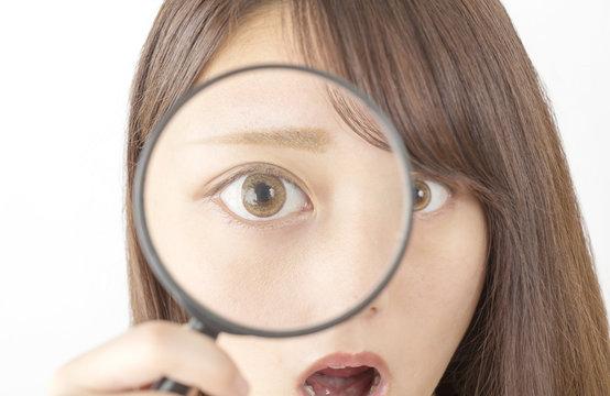 ビューティコンセプト 虫眼鏡で驚く女性