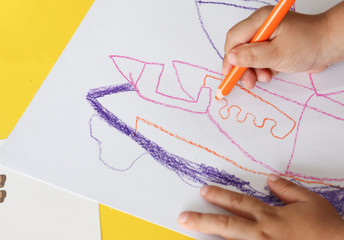 kid draws something with orange color pencil on white paper