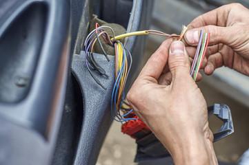 Mechanic's hands repairing electrical wires in the door of old car