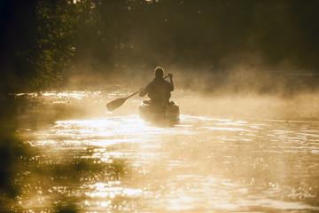 Ein Mann paddelt bei Morgenstimmung  in einem kanu einen  Fluss hinauf