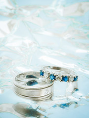 close up white diamond and blue gemstones on wedding rings with bright and shine background and copy space
