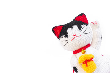 Japanese Lucky Cat Maneki Neko isolated on white background, the crochet cat doll is emerging on the right corner to leave middle area for copy space and your text.