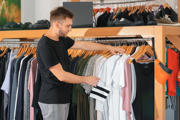 Young man choosing clothes in mall