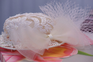 Wedding accessories: white lacy hat resting on a flowery cloth