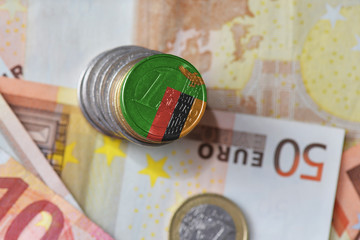euro coin with national flag of zambia on the euro money banknotes background.