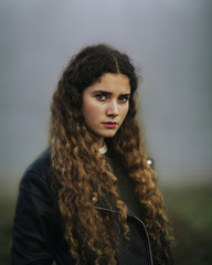 Beautiful young woman stands in the fog with leather jacket and looks straight at the camera