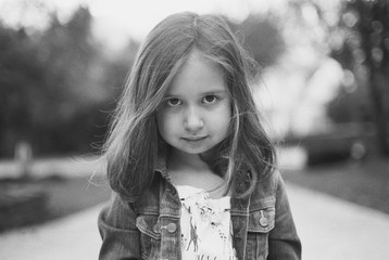 Black and white portrait of a cute young girl looking at camera