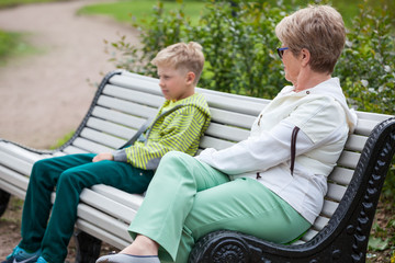 Grandmother tries to communicate with an abandoned grandson on a park bench