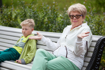 Grandmother gives her hands after unpleasant conversation to her grandson