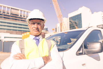 Senior builder man outdoors at construction site near his car lo
